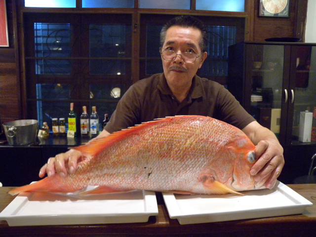 Japanese restaurant owner ready to cut the fish to slices
